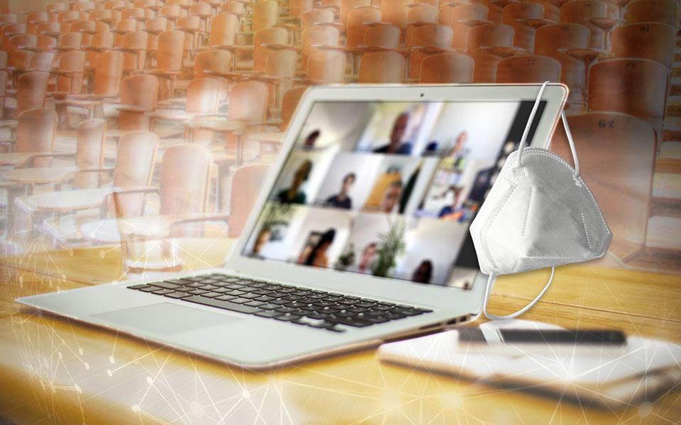 Laptop steht auf einem Tisch in einem leeren Hörsaal, rechts hängt eine weiße Maske